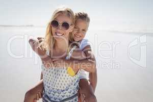 Happy mother piggybacking her daughter at beach
