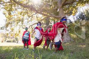 Group of friends in superhero costumes runing at campsite
