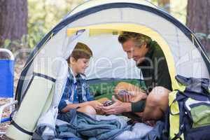 Happy father and son sitting inside tent in forest