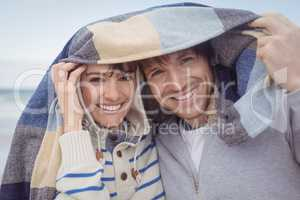 Portrait of smiling couple with blanket during winter