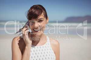Happy woman talking on mobile phone at beach