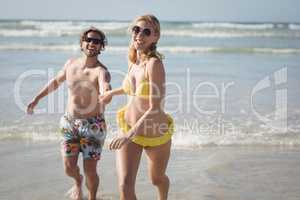 Happy young couple running on shore at beach`