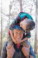 Portrait of happy father carrying son on shoulders