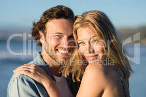 Portrait of happy couple hugging at beach