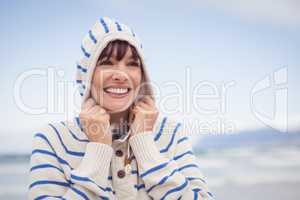 Smiling woman wearing hooded sweater during winter