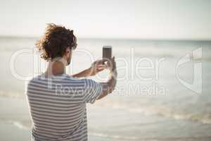 Rear view of man photographing sea at beach