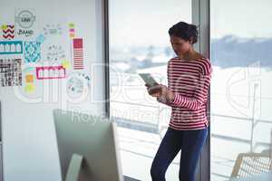 Female businesswoman using digital tablet while leaning on window in office