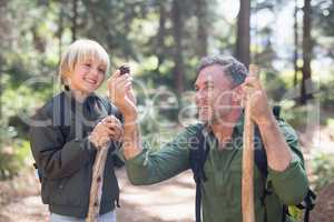 Cheerful father and son looking at pine cone in forest