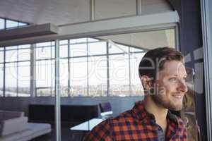 Smiling businessman looking through window