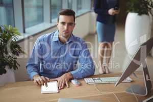 Portrait of executive using digital tablet at desk