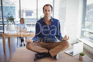 Executive meditating on desk