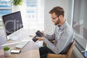 Executive looking at digital camera at desk