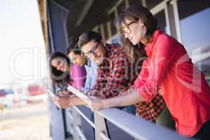 Business colleagues using tablet pc in balcony