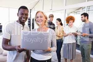 Portrait of smiling business people holding laptop with colleagues in background