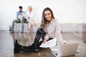 Portrait of businesswoman sitting by laptop on floor at creative office