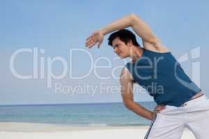 Man doing warm up on beach