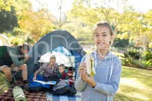 Smiling girl holding a sandwich while family sitting outside the tent