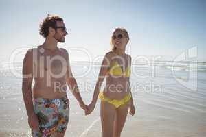 Happy young couple holding hands at beach during sunny day