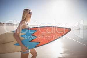 Woman carrying surfboard at beach during sunny day
