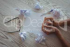 Hands of businesswoman crumpling papers on desk in office