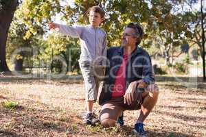 Happy man looking at boy pointing away in forest