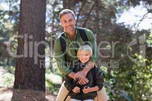 Happy father and son standing against trees in forest