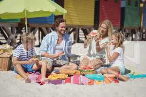 Happy family eating watermelon while sitting together at beach