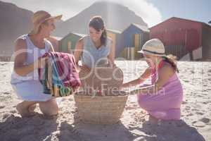 Happy multi-generation family by picnic basket at beach