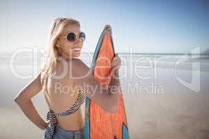 Portrait of smiling woman holding surfboard at beach