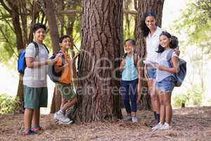 Happy students and teacher standing by tree