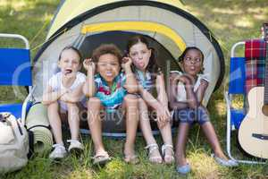 Children making face while sitting in tent at campsite