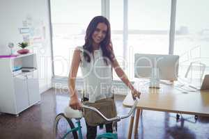 Beautiful businesswoman with bicycle in creative office