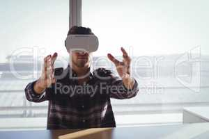 Businessman using virtual reality headset in creative office