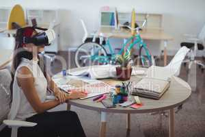 Businesswoman using virtual reality technology in creative office