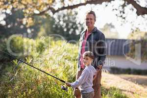 Portrait of father standing by boy holding fishing rod
