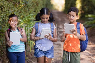 Boys and girls using digital tablets at natural parkland