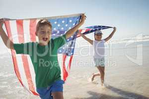Happy siblings holding American flags while running on shore