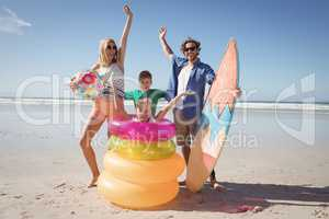 Cheerful family with arms raised at beach