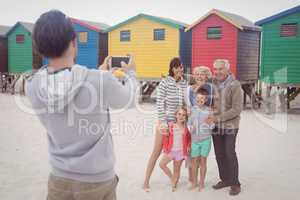 Man photographing family at beach