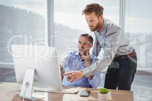 Executives discussing over personal computer at desk