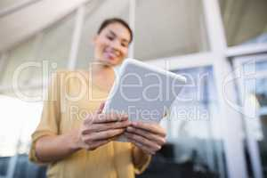 Low angle view of smiling businesswoman using tablet in office