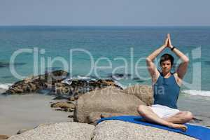 Full length of man meditating at beach