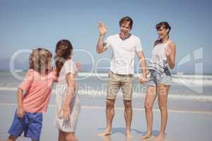 Happy parents waving hands while looking at children standing on shore