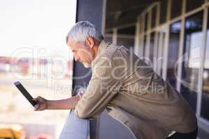 Mature businessman using tablet pc in balcony
