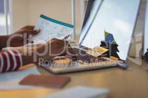 Businesswoman holding documents while using laptop in office