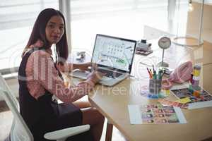 High angle portrait of businesswoman working on laptop at office desk