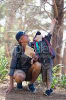 Boy pointing while man looking up in forest