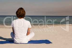 Rear view of man meditating at beach