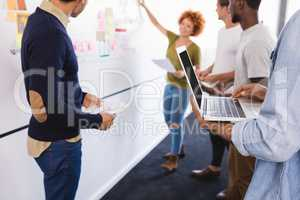 Colleagues standing by businesswoman explaining plan on whiteboard