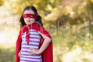 Little girl wearing superhero costume at campsite